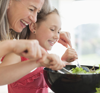 Grandmother and grandchild mixing a salad